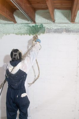 Jose Ramirez, a worker with Chicago Green Insulation, sprays foam insulation onto the walls of the Lyczko's home. It hardened and became part of the structure.